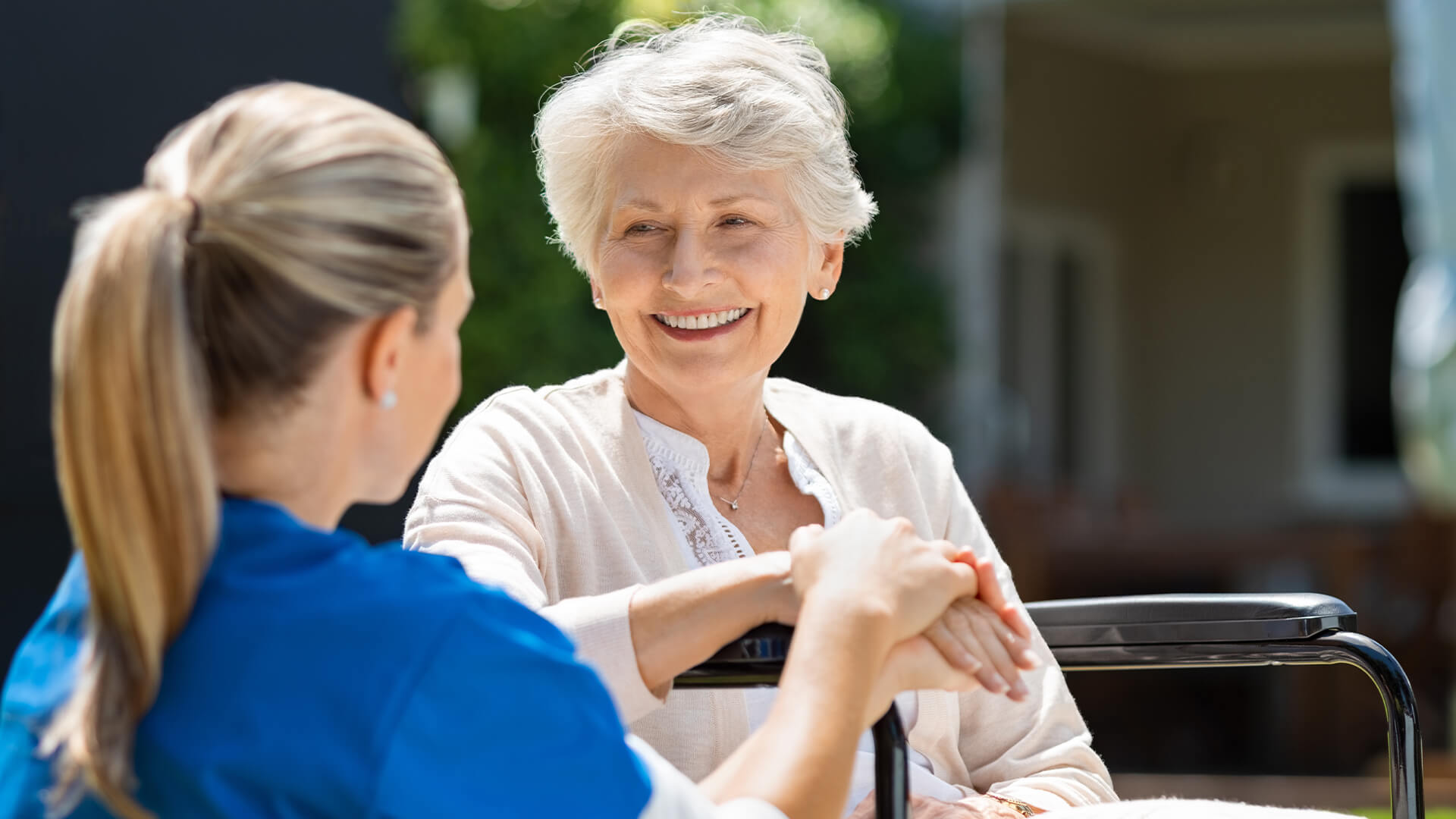 Older woman sitting outside with a younger woman caring for her