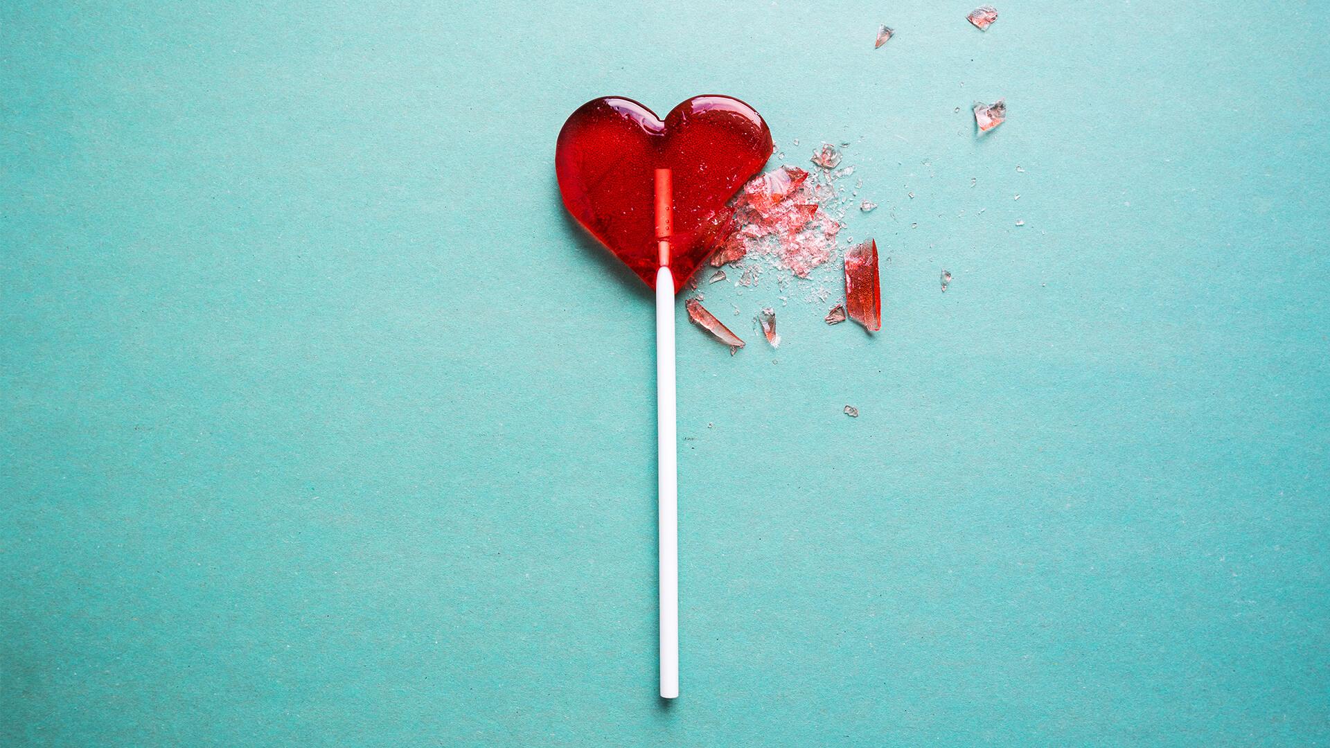 Broken heart-shaped lollipop on a blue background