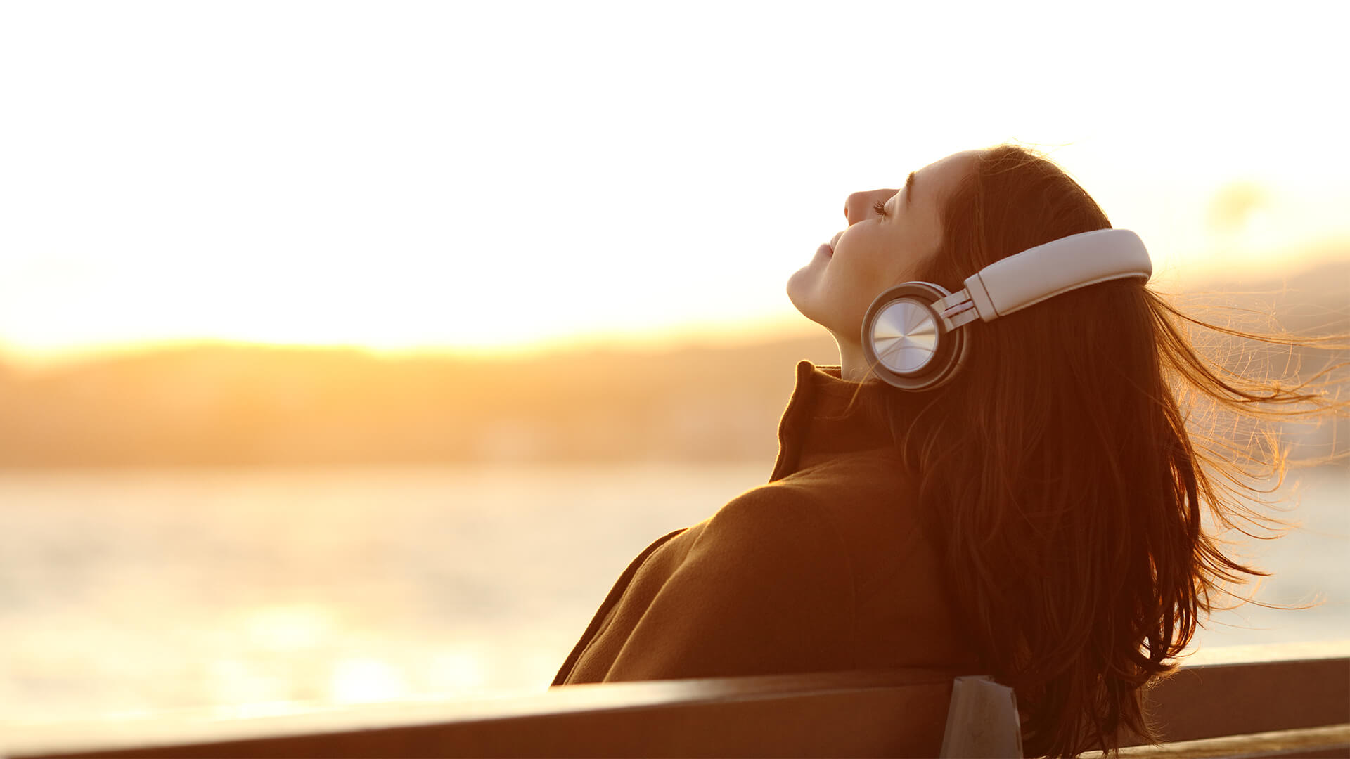 Woman listening to music outside at sunset