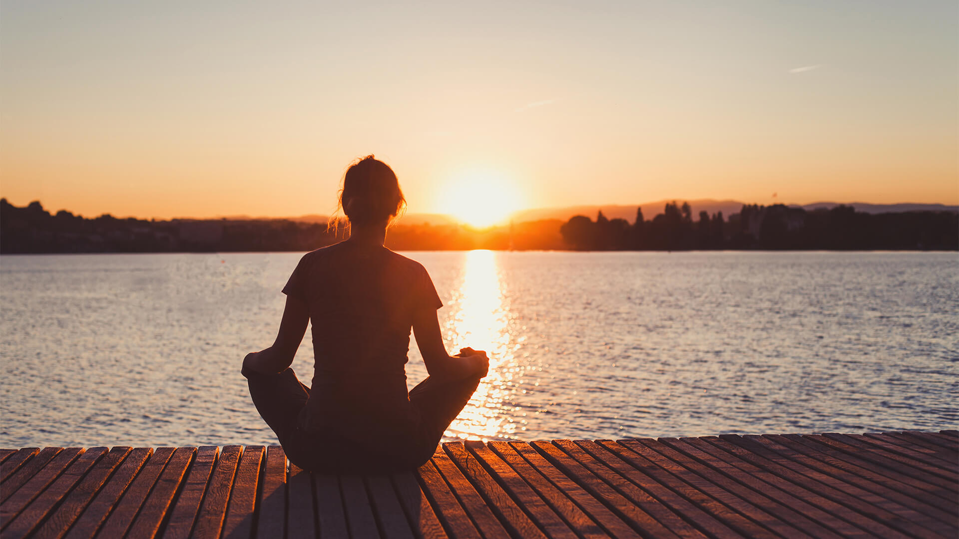 Woman meditating on a pier at sunset